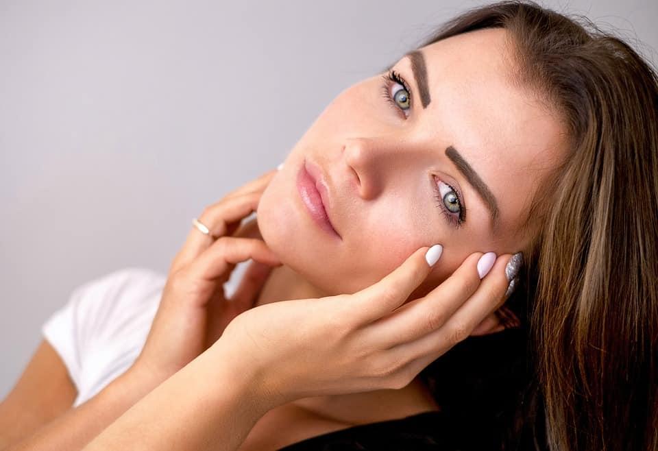 Junge Frau streift sich mit den Händen über das Gesicht