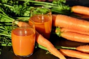 Möhren mit grün und 2 Gläser mit Karottensaft